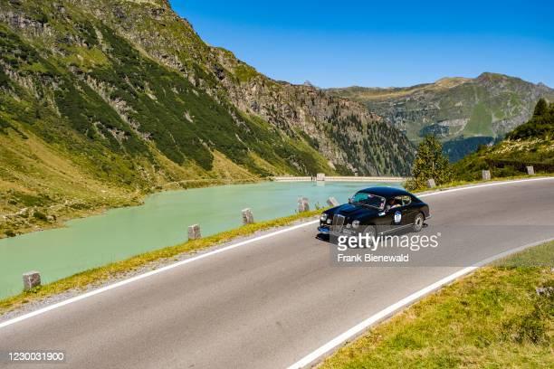 Vintage car Lancia Aprilia Berlina driving past a lake on Silvretta Hochalpenstrasse during the Arlberg Classic Car Rally.
