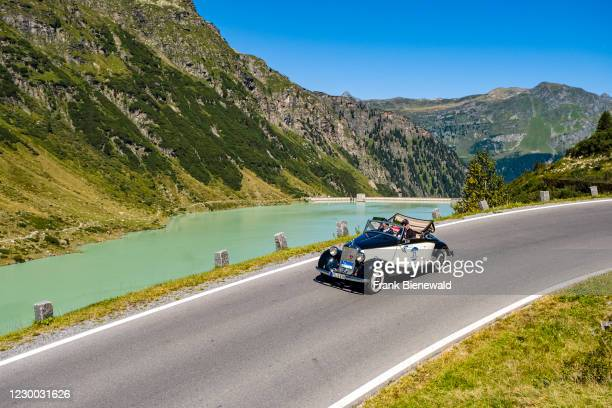 Vintage car Mercedes-Benz 170 V Cabrio driving past a lake on Silvretta Hochalpenstrasse during the Arlberg Classic Car Rally.