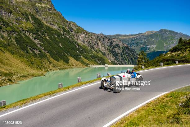 Vintage car Mercedes-Benz SSKL driving past a lake on Silvretta Hochalpenstrasse during the Arlberg Classic Car Rally.
