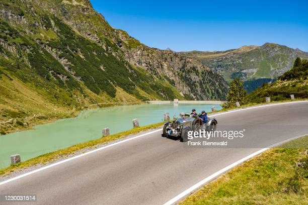 Vintage car MG TA Midget Special K 3 driving past a lake on Silvretta Hochalpenstrasse during the Arlberg Classic Car Rally.