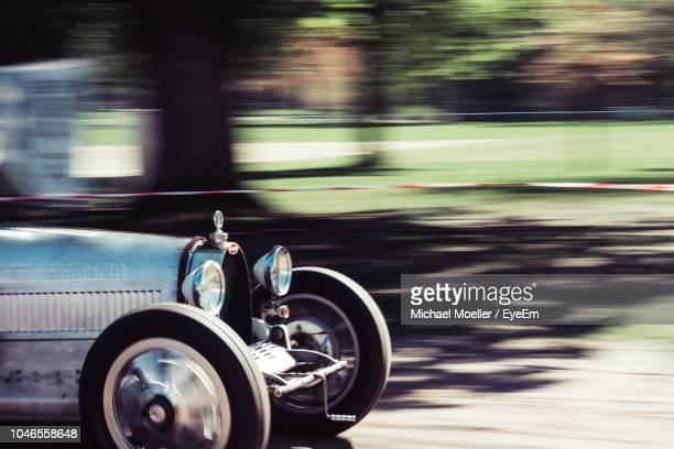 vintage car moving on road at park - old car stock pictures, royalty-free photos & images
