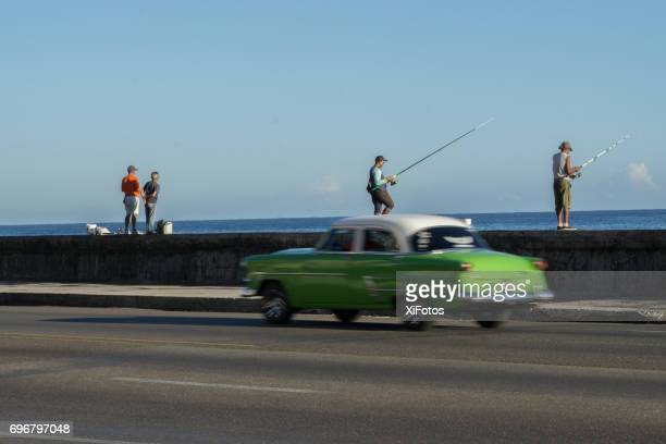 Oldtimer auf Havannas Malecon während Männer Fischen vor der Küste