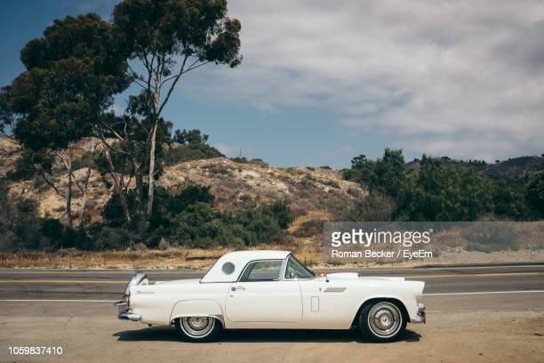 vintage car on road against sky - vintage car stock pictures, royalty-free photos & images
