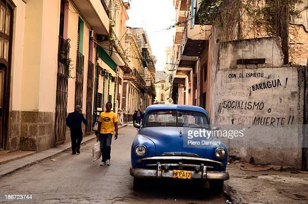 CONTENT] Vintage car parked in Havana Cuba surrounded by old decaying buildings and communist slogans