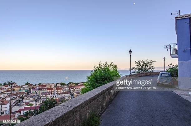 vintage car parked on road by sea against clear sky - calabria stock pictures, royalty-free photos & images