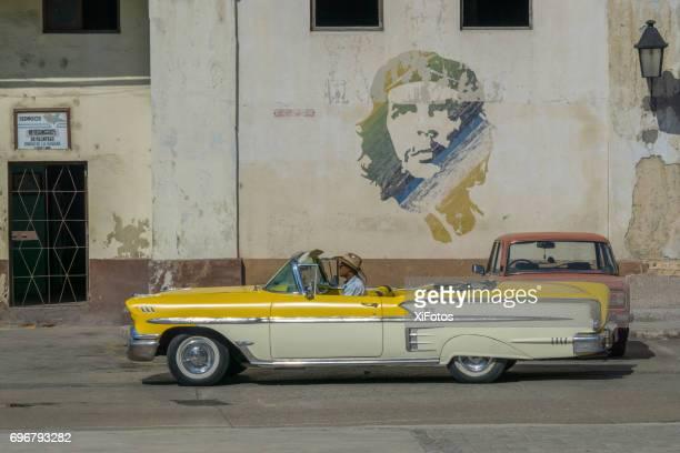 Coches de época pasa por el icono del Che Guevara en la pared en la Habana