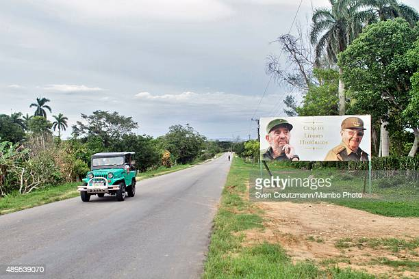 US vintage car passes past a propaganda sign with the images of Cubas Revolution leader Fidel Castro and his brother Raul Castro President of Cuba...
