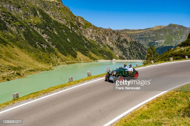 Vintage car Riley 12/4 Special Sport 2 Seats driving past a lake on Silvretta Hochalpenstrasse during the Arlberg Classic Car Rally.