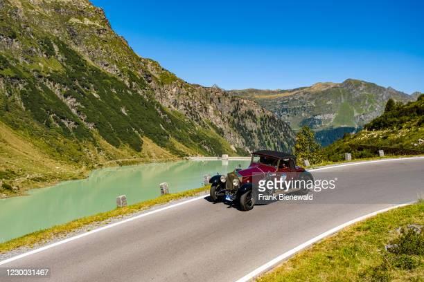 Vintage car Rolls Royce Phantom I Roadster driving past a lake on Silvretta Hochalpenstrasse during the Arlberg Classic Car Rally.