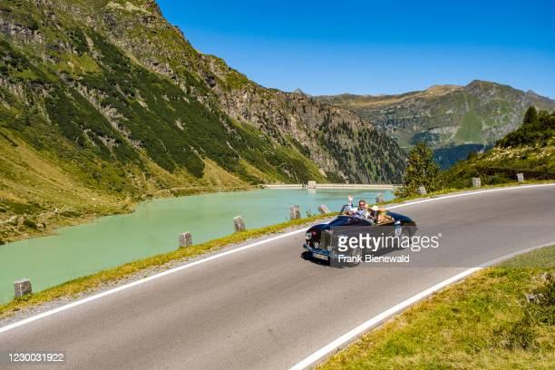 Vintage car Sunbeam Alpina Mark I Cabrio driving past a lake on Silvretta Hochalpenstrasse during the Arlberg Classic Car Rally.
