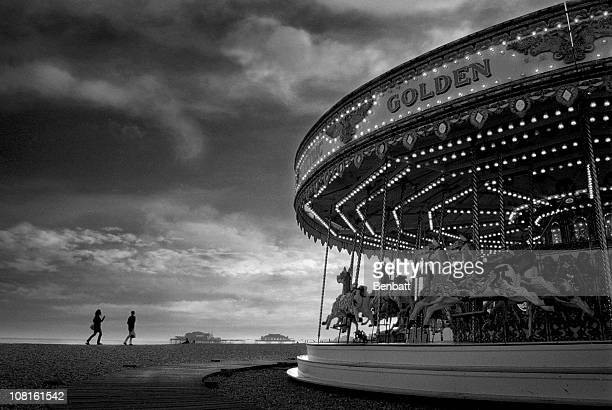 vintage carousel and people walking on brighton beach - brighton beach england stock pictures, royalty-free photos & images