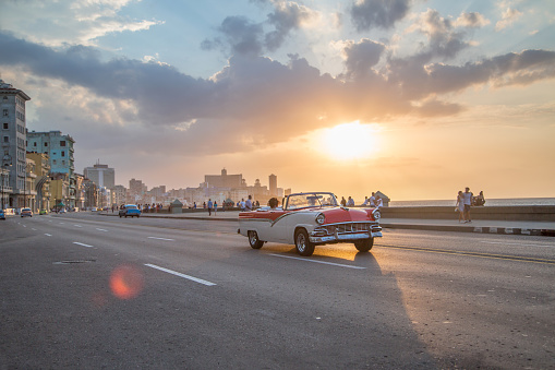 Vintage cars driving along Malecon, Havana as sun goes down - gettyimageskorea