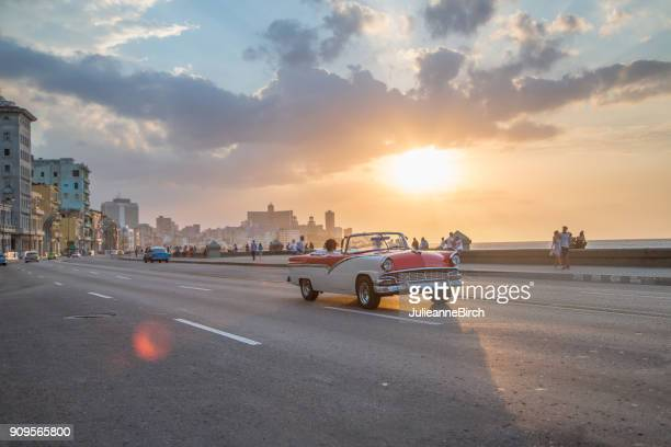 Vintage cars driving along Malecon, Havana as sun goes down