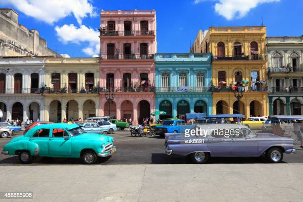 vintage cars moving on the streets of colorful havana - old havana stock pictures, royalty-free photos & images
