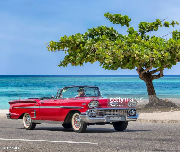 Vintage classic red cabriolet american oldtimer car near Havana Cuba at beach