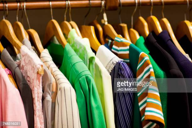 vintage clothes on clothes rail in antique and vintage emporium - clothes rack stock pictures, royalty-free photos & images