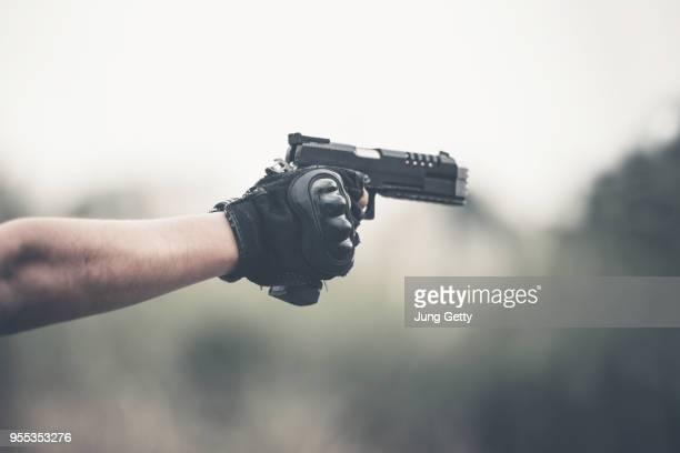 a vintage color photo selective focus  man's hand holding a gun. 9 mm pistol. - objetivo militar imagens e fotografias de stock