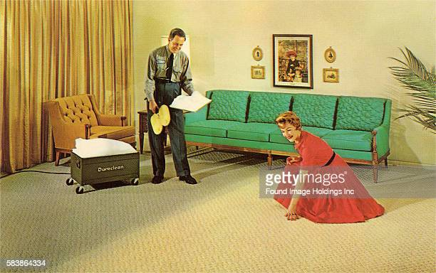 Vintage color photograph of a housewife in a red dress kneeling on the yellow carpet in her living room admiring the good job done by the uniformed...