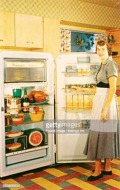 Vintage color photograph of a kitchen interior in which a housewife wearing a dress with a white apron stands in front of a fully loaded open...