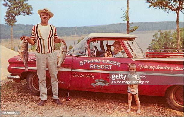 Vintage color photograph of a red Chevrolet El Camino truck parked above a lake with a man standing beside it holding two large freshly caught bass a...
