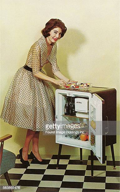 Vintage color photograph of a woman in a chic polka dot dress and heels taking a platter of food out of a mini-fridge, elevated on slim legs on a...