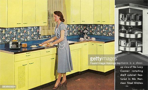 Vintage color photograph of a woman in a dress and heels standing in a kitchen with yellow steel cabinets and a steel countertop preparing toast in a...
