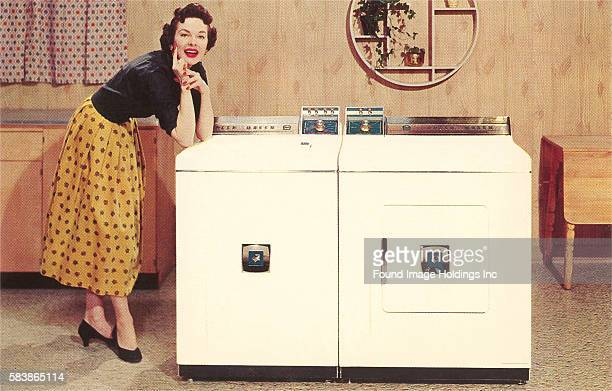 Vintage color photograph of a woman in skirt and heels leaning on a freestanding washer and dryer in a paneled 50s room, 1950s.