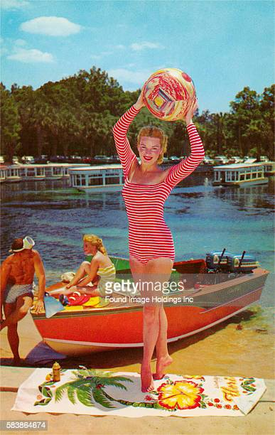 Vintage color photograph of a woman standing on tiptoe on a beach towel wearing a longsleeved red and white striped leotard and holding a beach ball...