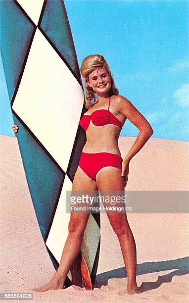 Vintage color photograph of a young woman in a red bikini and teased blond hair standing the beach holding a blue and white diamond longboard 1960s
