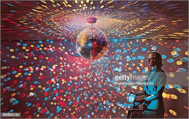 Vintage color photograph of a young woman in glasses and a blue suit manipulating an apparatus that produces a colorful bubble light display covering...