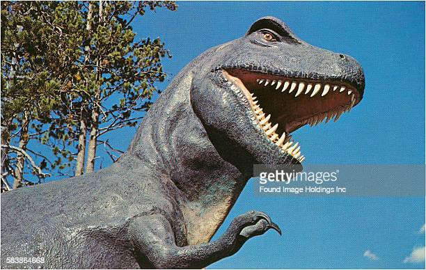 Vintage color photograph of an openmouthed Tyrannosaurus Rex sculpture against a blue sky