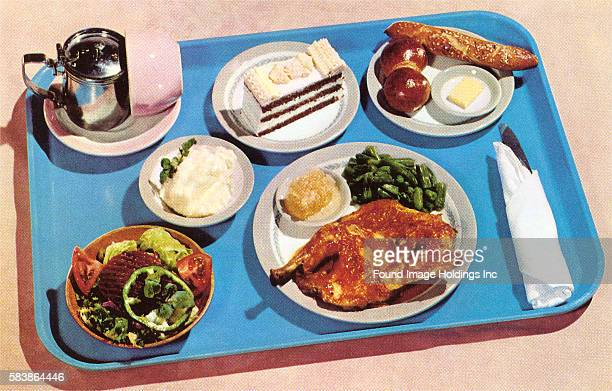 Vintage color photograph of of a blue plastic tray holding a complete dinner on five different plates including a main course rolls salad potatoes...