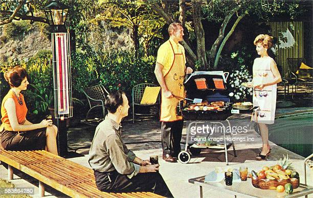 Vintage color photograph of two couples at a poolside backyard barbecue with one of the husbands manning the grill in a yellow apron as his wife...