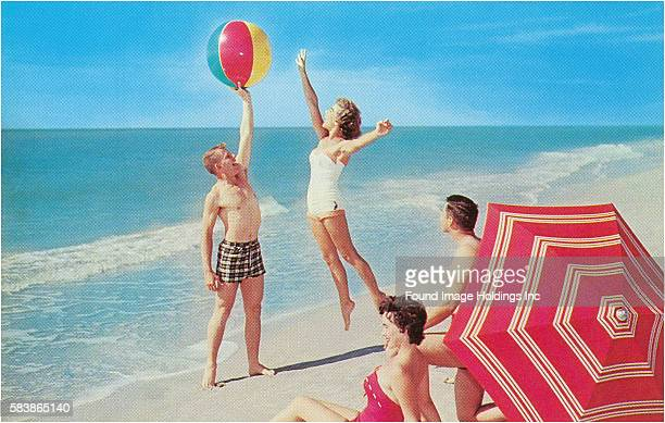Vintage color photograph of two couples at the beach in bathing suits sitting in the sand near a red umbrella and playing with a beachball at the...