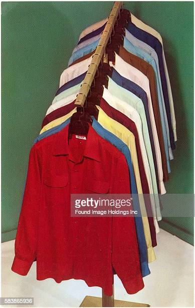 Vintage color studio photograph of a casual tailored red blouse on a clothes hangar, hung on an ascending rack, the same style blouse repeated in...
