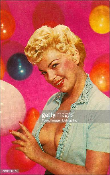 Vintage color studio photograph of a coyly smiling buxom blonde with an unbuttoned demure blue blouse revealing braless breasts all against a hot...