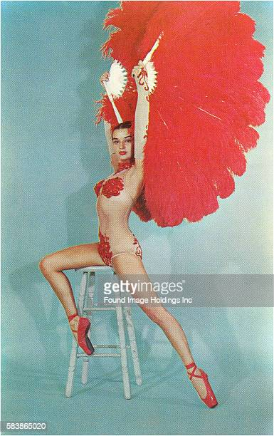 Vintage color studio photograph of a stunning showgirl in a transparent bodysuit with red beading offering some coverage bright red lipstick and red...