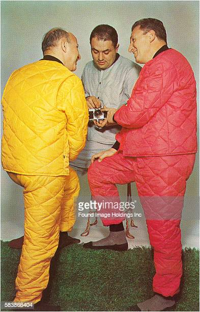 Vintage color studio photograph of three men in different colored quilted jackets and pants perhaps expedition weight pajamas standing in a cluster...