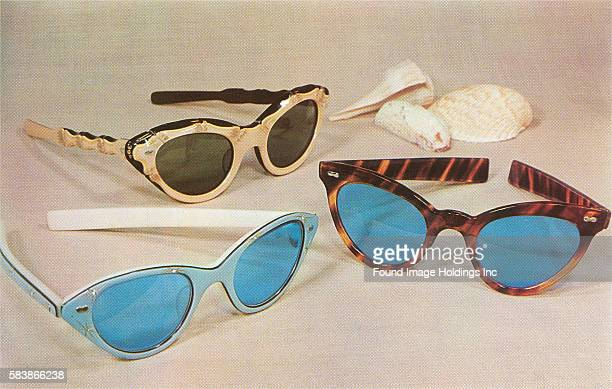Vintage color studio photograph of three pairs of sunglasses with decorative frames and lenses on a sandcolored background with seashells 1950s