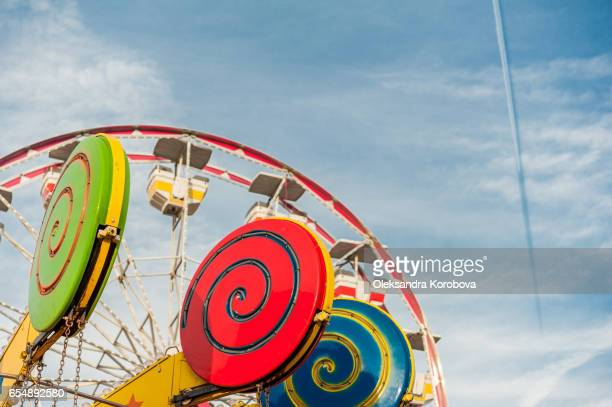 vintage colorful ferris wheel against a sunny blue sky. - canadian national exhibition stock photos and pictures