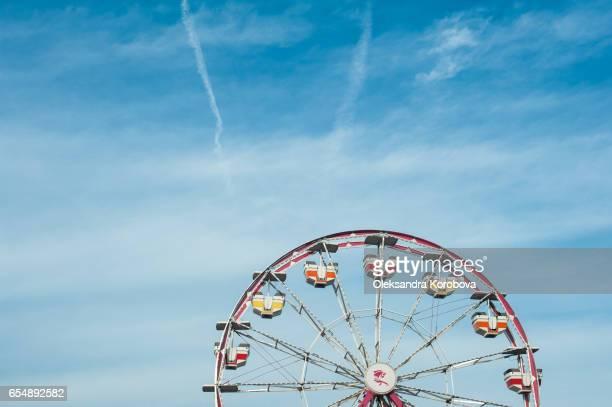 Vintage colorful ferris wheel against a sunny blue sky.