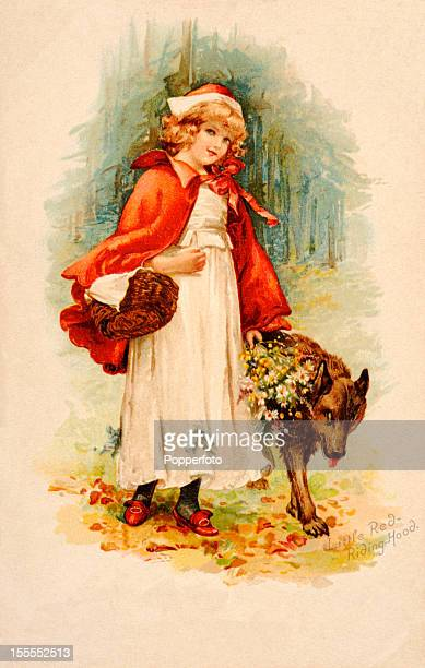 A vintage colour illustration featuring Little Red Riding Hood with a wolf published as a Christmas greeting card circa 1902