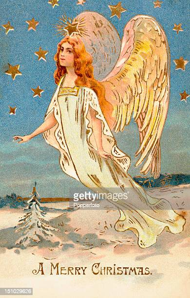 A vintage colour postcard featuring an illustration of an angel and Christmas greetings circa 1910