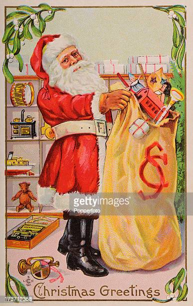 A vintage colour postcard featuring Santa Claus filling a sack full of toys in his workshop and bringing Christmas greetings circa 1900