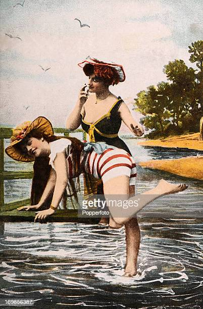 Vintage coloured photograph of two young ladies in a seaside studio setting, circa 1910.