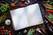 Vintage cookbook with spices and herbs on rustic wooden background