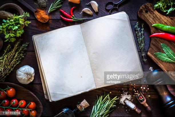 vintage kookboek met kruiden en kruiden op rustieke houten achtergrond - keukengereedschap stockfoto's en -beelden