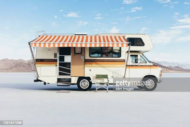 vintage dodge sportsman rv with striped canopy parked on salt flats - cadeira dobrável - fotografias e filmes do acervo