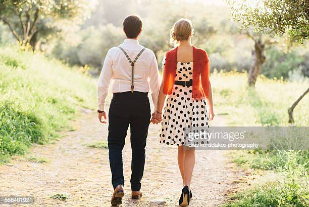 Vintage dressed couple walking hand in hand