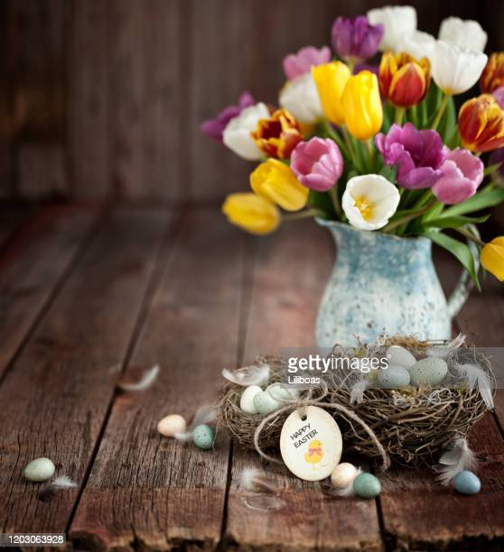 vintage easter tulips and easter eggs on an old wood background - easter flowers stock pictures, royalty-free photos & images